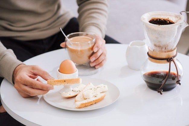 Fresh delicious breakfast with soft boiled egg, crispy toasts and cup coffee in living room