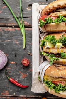 Свежие вкусные гамбургеры с овощами на деревенском деревянном фоне. концепция быстрого питания и нездоровой пищи. вертикальное изображение. вид сверху. место для текста