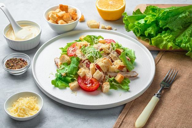 灰色の背景に新鮮でおいしいシーザーサラダ、ソース、チーズ、レタス。側面図、水平。