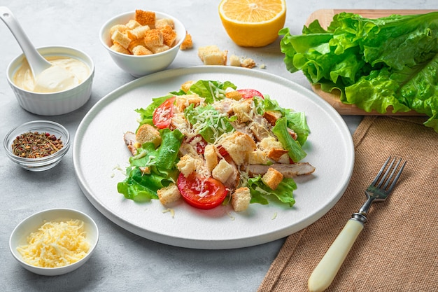Fresh, delicious caesar salad, sauce, cheese and lettuce on a gray background. side view, horizontal.