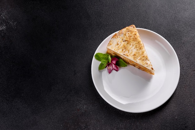 Fresh delicious carrot cake with cream on a dark background. carrot cake with whipped frosting