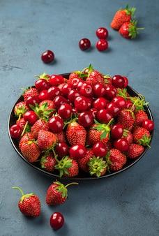 회색 파란색 배경에 신선한 맛있는 체리와 딸기. 세로 보기입니다. 건강한 여름 과일과 열매.