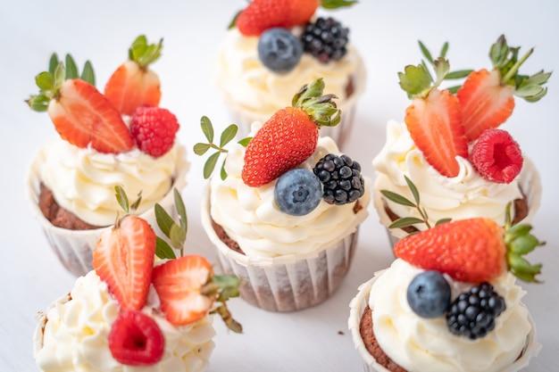 요구르트 크림과 신선한 딸기와 신선하고 맛있는 컵 케이크. 확대