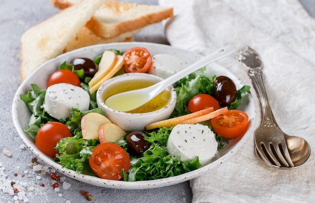 Fresh, delicious goat's cheese salad with lettuce, cherry tomatoes, apple, kalamata olives