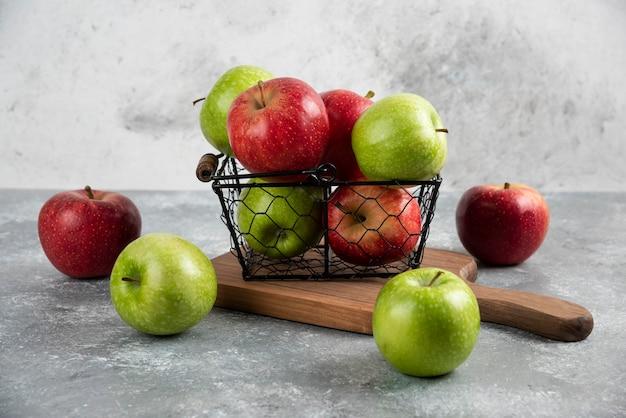 Свежие вкусные зеленые и красные яблоки в металлической корзине.
