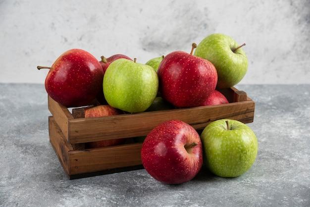 木製の箱に新鮮なおいしい緑と赤のリンゴ。