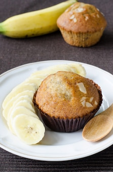 Fresh delicious homemade banana cup cake in dark brown paper with fresh banana