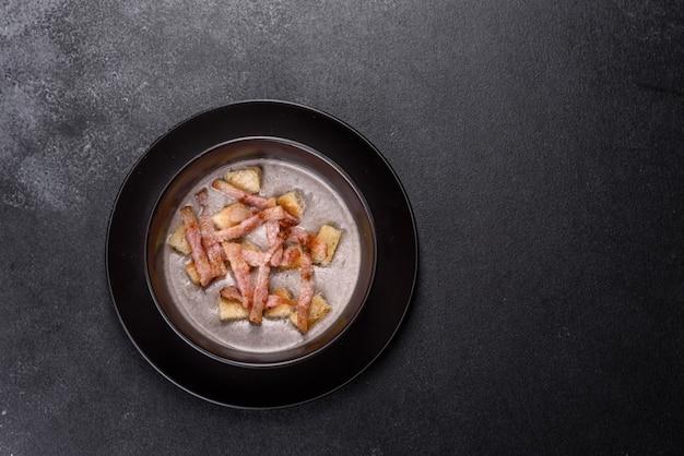 검은 접시에 버섯과 베이컨을 곁들인 신선한 맛있는 뜨거운 퓌레 수프
