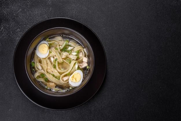 검은 접시에 국수와 메추라기 달걀을 곁들인 신선한 맛있는 뜨거운 수프