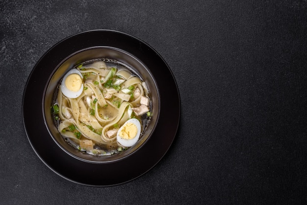 Fresh delicious hot soup with noodles and quail egg in a black plate