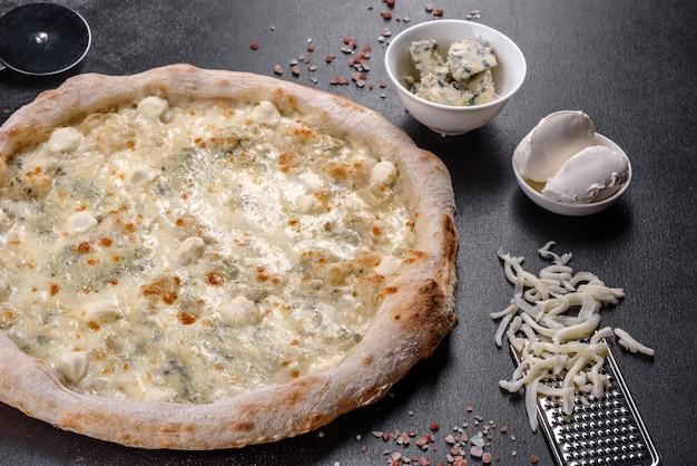어두운 콘크리트 배경에 4가지 종류의 치즈를 넣은 신선하고 맛있는 이탈리아 피자. 이탈리아 요리