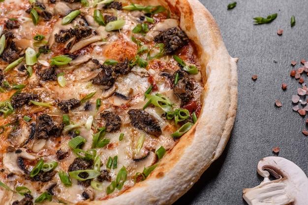 暗いコンクリートの背景に肉、マッシュルーム、トマトを使った新鮮でおいしいイタリアンピザ。イタリア料理
