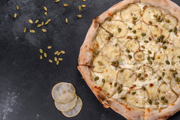 어두운 콘크리트 배경에 배와 호박 씨를 넣은 신선한 맛있는 이탈리아 피자. 이탈리아 요리