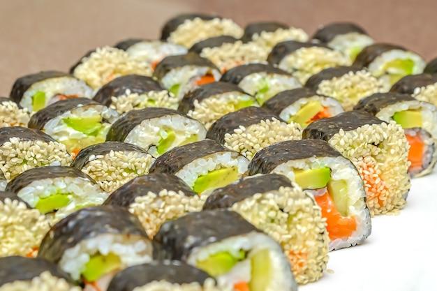 Свежие вкусные японские суши с авокадо, огурцом, креветками, крупным планом.