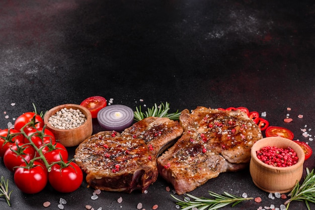 Fresh delicious juicy steak on the bones with vegetables and spices. pork juicy steak grill on dark table