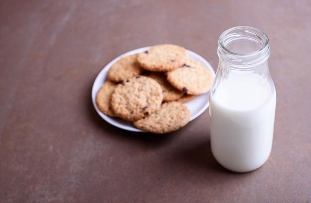 白いプレートにチョコレートクッキーとテクスチャ背景のガラス瓶に新鮮なおいしい牛乳。テキストの場所。