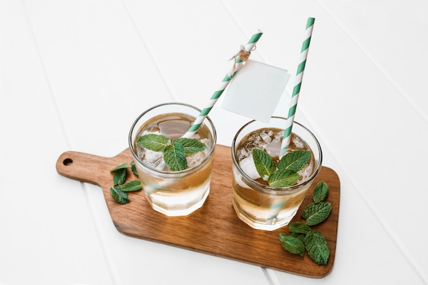 Fresh delicious mojito with straw and label on wood plank