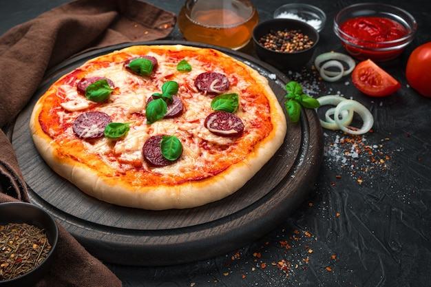 茶色の背景に新鮮でおいしいピザと食材。コピースペースのある側面図。
