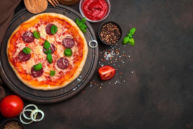 茶色の背景に新鮮でおいしいピザと食材。コピースペースのある上面図。料理の背景の概念。