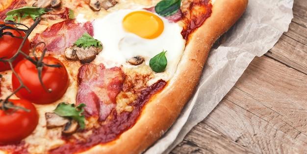 オーブンで焼いた新鮮でおいしいピザに卵、生ハム、トマトを添えて