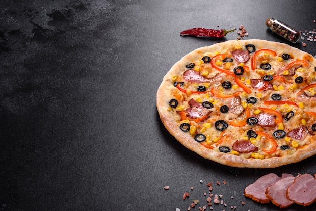 Fresh delicious pizza made in a hearth oven with olives, chili pepper and ham