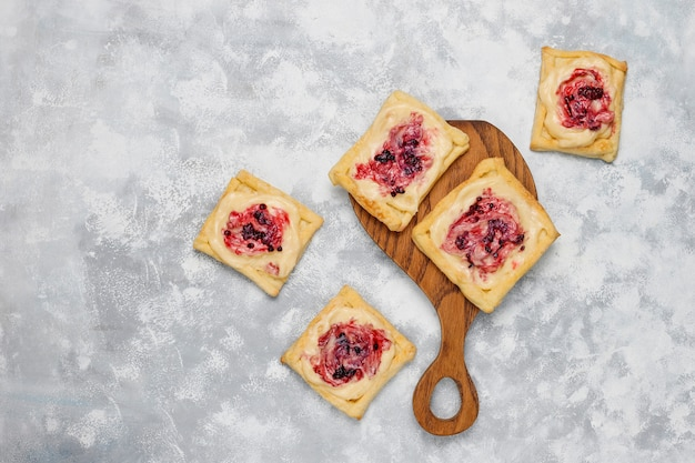 Fresh delicious puff pastry with berry jam and heavy cream on concrete