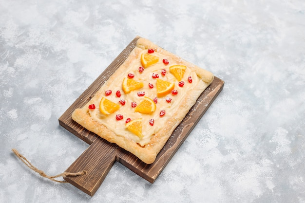 Fresh delicious puff pastry with pomegranate seeds and orange slices on concrete
