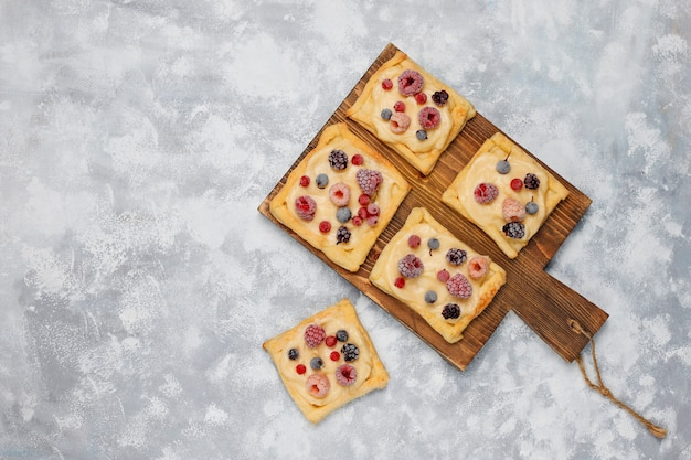 Fresh delicious puff pastry with sweet berries on concrete