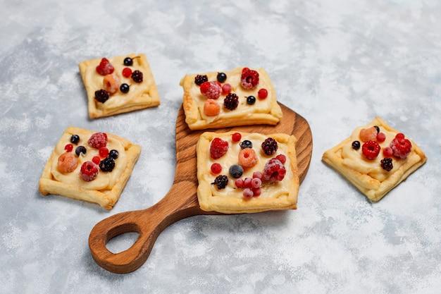 Свежее вкусное слоеное тесто со сладкими ягодами на бетоне