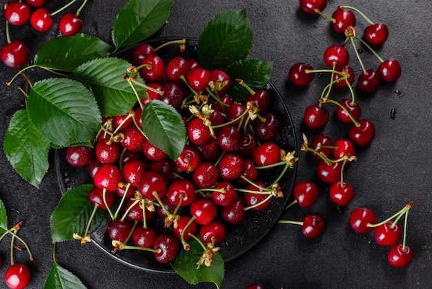 夏の庭で引き裂かれた新鮮なおいしい赤い明るい桜の果実