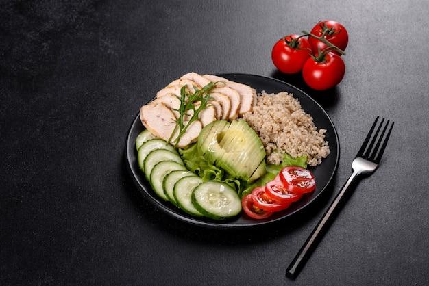Свежий вкусный салат с киноа, курицей и свежими овощами на тарелке