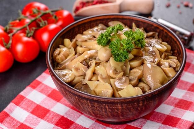 Свежие вкусные пряные консервированные грибы со специями и зеленью в керамической посуде на темном бетонном фоне