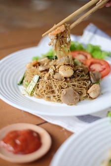 Fresh delicious vietnamese noodle vermicelli with pieces of meatballs and tomato on the white plate