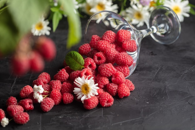 Fresh deluxe raspberries in martini glass with field flowers on dark wooden