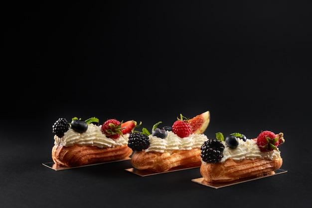 分離された列のクリームで満たされた自家製エクレアの新鮮なデザート