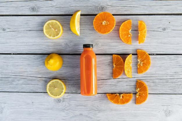 나무 배경에 병에 과일과 야채에서 신선한 해독 주스