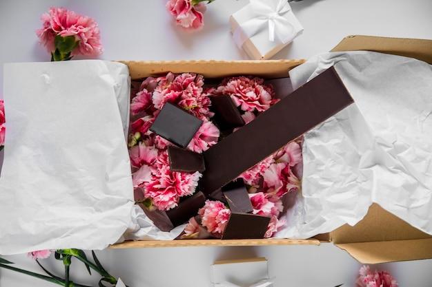白いテーブルの上のギフトボックスに新鮮なナデシコの花とチョコレート。夏の時間の概念