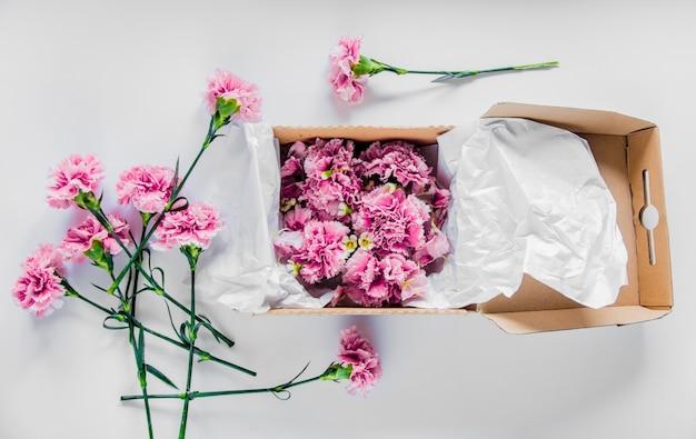白いテーブルの上の箱に新鮮なナデシコの花。夏の時間の概念