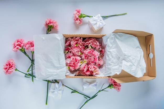 白いテーブルの上のギフトボックスに新鮮なナデシコの花。夏の時間の概念