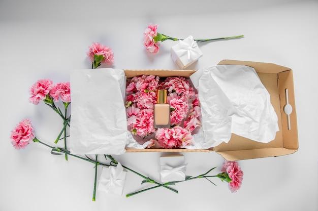 白いテーブルの上にクリーム色のファンデーションとホリデーボックスに新鮮なナデシコの花。夏の時間の概念