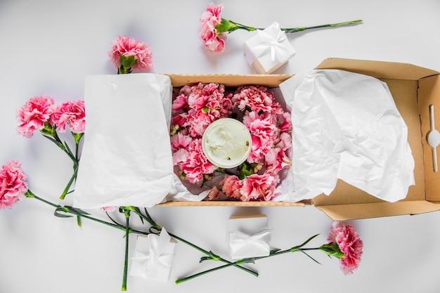 白いテーブルの上のクリームとホリデーボックスに新鮮なナデシコの花。夏の時間の概念