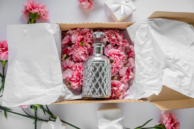 흰색 테이블에 향수와 휴일 상자에 신선한 패 랭이 꽃. 여름 시간 개념