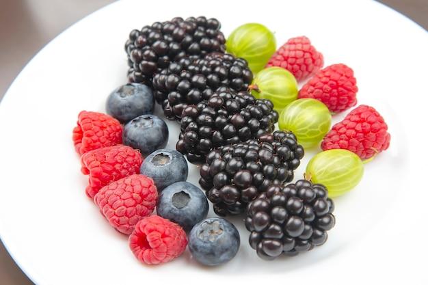 하얀 접시에 신선한 다른 열매입니다. 유용한 비타민 건강 식품 과일. 건강한 야채 아침 식사