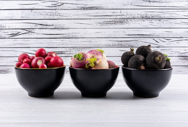 Fresh different color radishes in a three black bowls on a white wooden table.