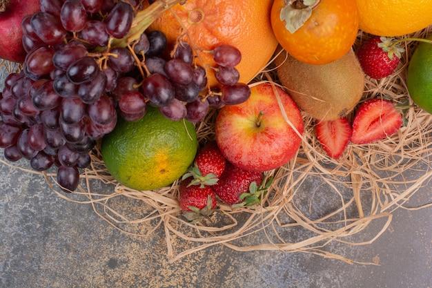 Свежие разные фрукты на мраморной поверхности
