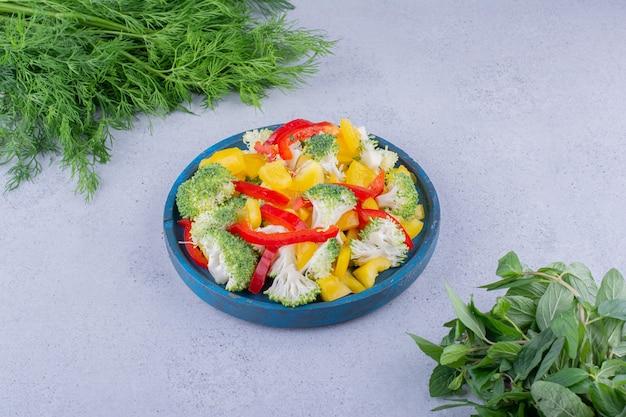 Aneto fresco e fasci di menta accanto a un piatto di insalata su sfondo marmo. foto di alta qualità