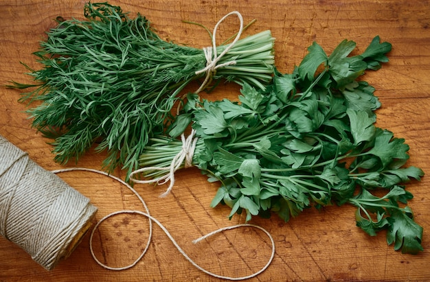 Fresh dill and parsley greens on wooden table