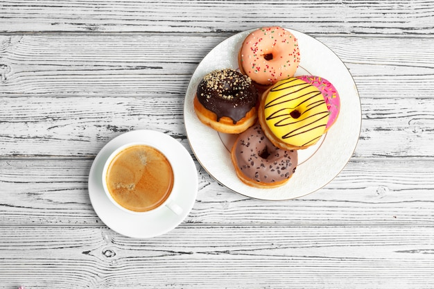 Fresh donut with coffee on wooden surface