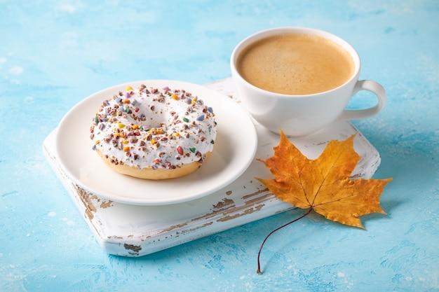 一杯のコーヒーと秋のカエデの葉と新鮮なドーナツ。秋のコンセプト