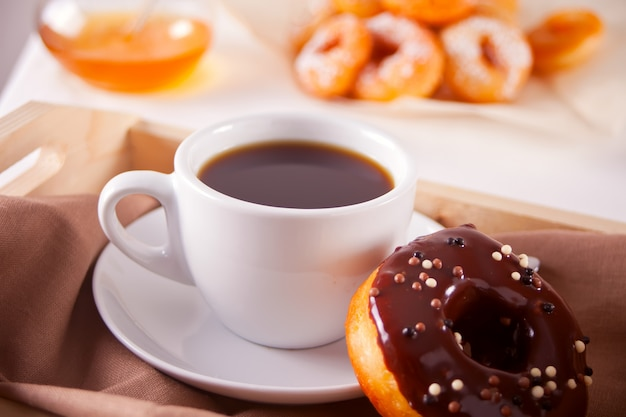 Fresh donuts with cup of coffee on the wooden table